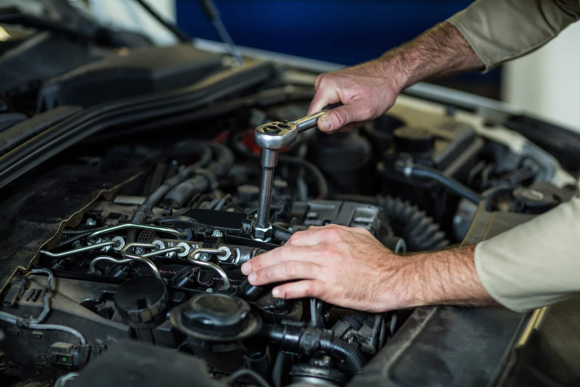 Mécanicien qui travaille sur le moteur d'une voiture