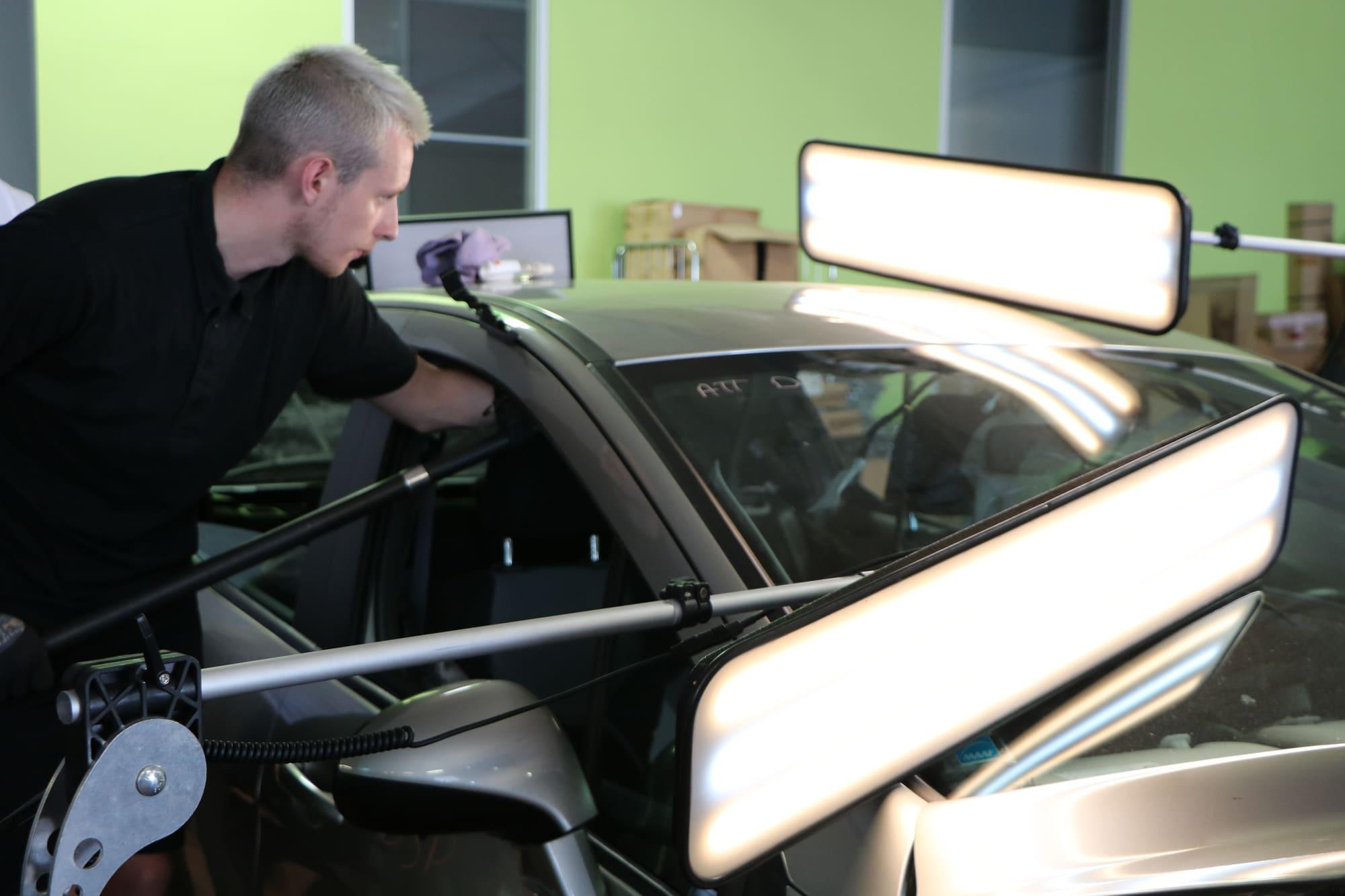 Carrossier chez SAFRA Automobile qui utilise une technique de débosselage sans peinture sur un véhicule grêlé