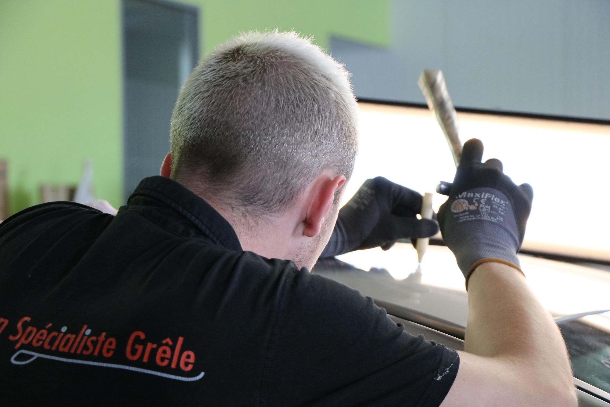 Carrossier qui utilise une technique de débosselage sans peinture sur un véhicule grêlé