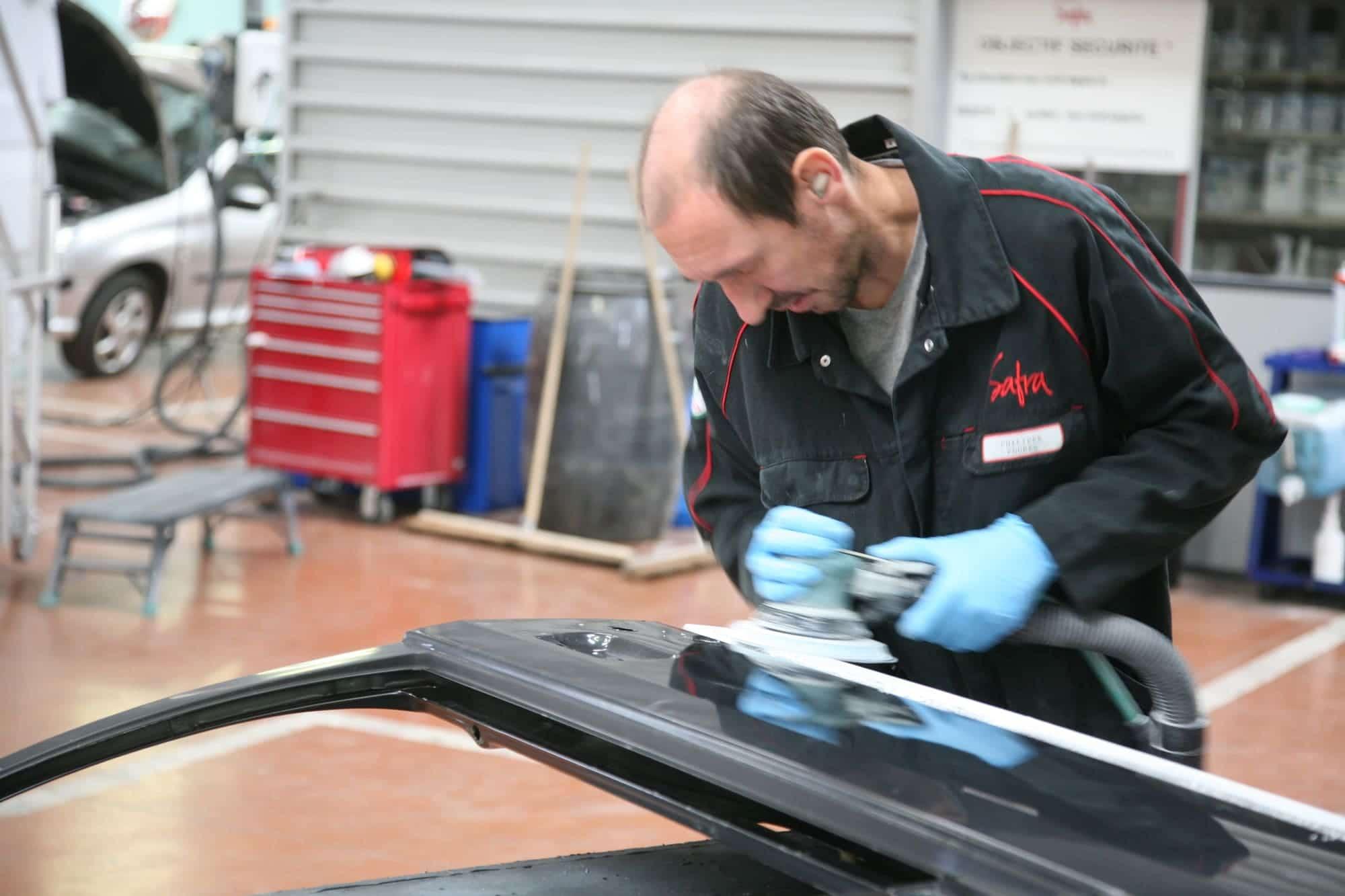 Carrossier de SAFRA Automobile qui ponce la carrosserie d'un véhicule