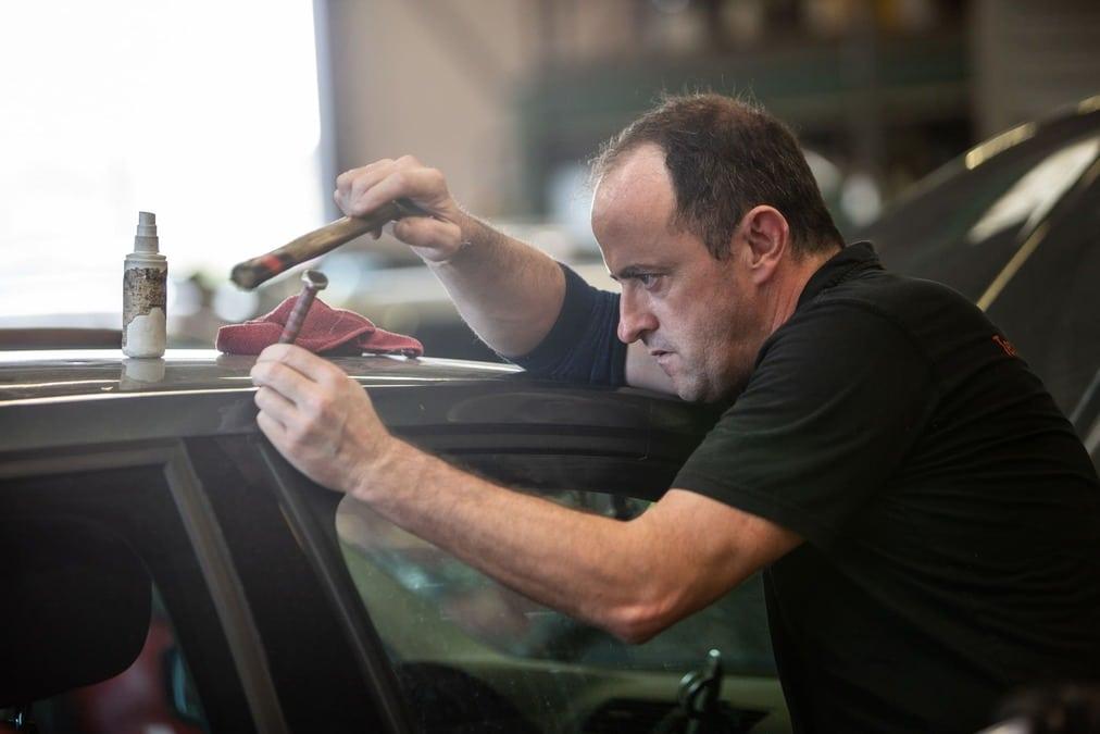 Carrossier SAFRA Automobile qui utilise une technique de débosselage sans peinture sur une voitue