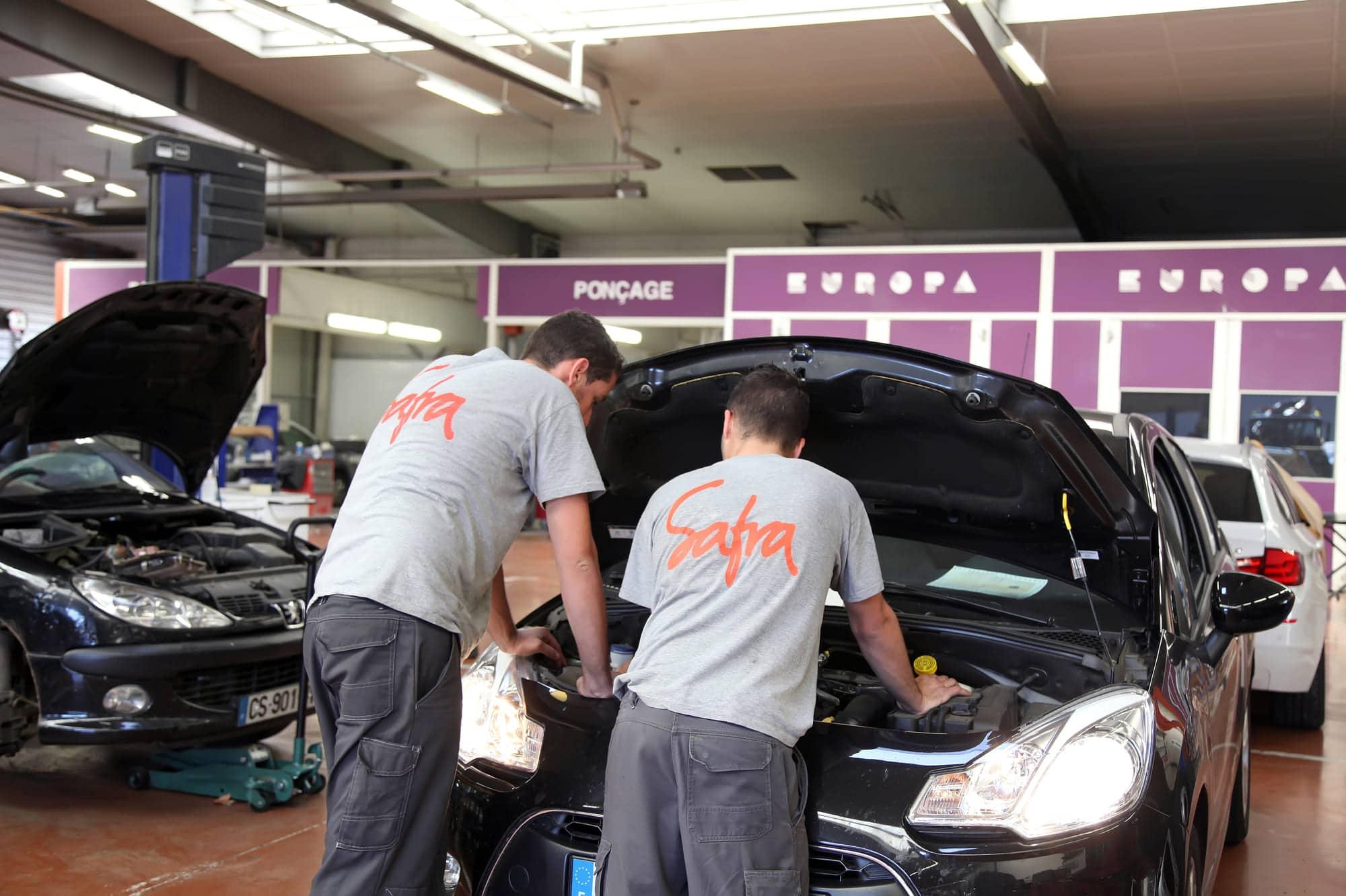 Deux mécaniciens de SAFRA Automobile qui regarde dans le capot d'une voiture dans les ateliers